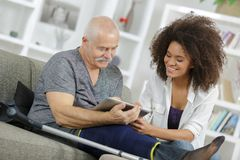 Young woman and senior man chating with family using tablet. Young women and senior men chating with family using tablet young royalty free stock photography