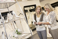 Young woman with senior mother looking at footwear in bridal store Stock Photography