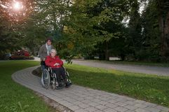 Young woman with senior woman sitting in wheelchair  royalty free stock photography