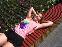 Young woman serenely lying on the bench in a park sunbathing Stock Photography