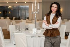 Young woman is serving a festive table in a restaurant standing near the dinner table royalty free stock images