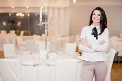 Young woman is serving a festive table in a restaurant standing near the dinner table royalty free stock photos
