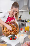 Young woman serving food in the kitchen - making breakfast for t Stock Images