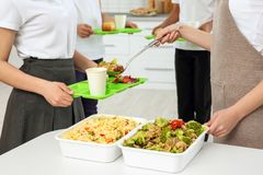 Young woman serving lunch to school girl. At canteen Royalty Free Stock Photos