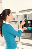 Young woman setting coffee maker machine kitchen Royalty Free Stock Photo