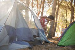 Young woman setting up tent on field Stock Image