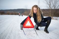 Young woman setting up a warning triangle Stock Image