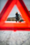 Young woman setting up a warning triangle and calling for assistence Stock Photography