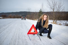 Young woman setting up a warning triangle and calling for assistence Stock Images