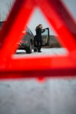 Young woman setting up a warning triangle and calling for assistence Stock Photos