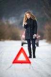 Young woman setting up a warning triangle and calling for assistence Royalty Free Stock Photography