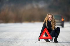 Young woman setting up a warning triangle Royalty Free Stock Image