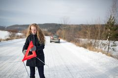 Young woman setting up a warning triangle Royalty Free Stock Photography