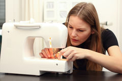 Young woman sewing. On Sewing Mashine Stock Image