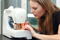 Young woman sewing. On sewing Mashine Royalty Free Stock Photography