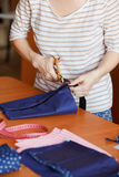 Young woman sewing at home, hemming blue fabric. Fashion designer creating new fashionable styles. Dressmaker makes Royalty Free Stock Photography