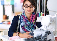 Young woman sewing while sitting at her working Stock Images