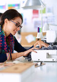 Young woman sewing while sitting at her working Royalty Free Stock Image