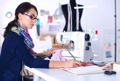 Young woman sewing while sitting at her working place Stock Photos