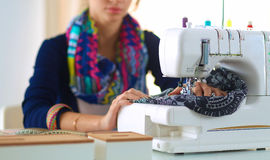 Young woman sewing while sitting at her working place Stock Photo