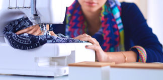 Young woman sewing while sitting at her working place Royalty Free Stock Image