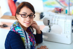 Young woman sewing while sitting at her working place.  royalty free stock photography