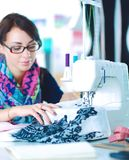 Young woman sewing while sitting at her working place.  royalty free stock photo