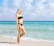 Young woman in a sexy bikini posing on the beach Stock Photos