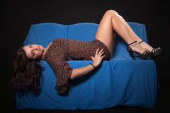 Young woman in sexy dotted mini dress. Lying on blue sofa on a black background Royalty Free Stock Photo