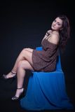 Young woman in sexy dotted mini dress. Sitting on a blue chair on a black background Stock Image