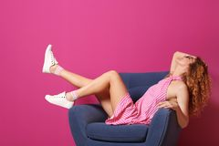 Young woman with legs in armchair. On color background stock image