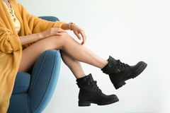 Young woman with legs in armchair. On light background stock photo