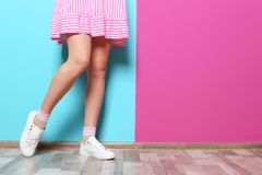 Young woman with legs near wall. Young woman with legs near color wall stock images