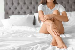 Young woman with legs resting on bed. At home royalty free stock images