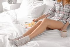 Young woman with legs resting on bed. At home stock images