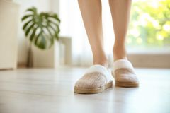 Young woman with legs in soft slippers. At home stock photography