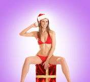 A young woman in sexy Santa clothes on a present Royalty Free Stock Photo