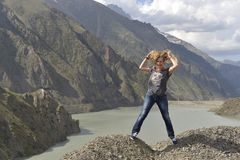 A young woman with shaggy hair laughs while standing on the edge of a cliff above a lake. stock photos