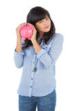 Young woman shaking her piggy bank Stock Images