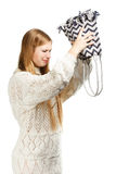 Young woman shaking out her bag in search. Young beautiful woman in white knitted sweater shakes out her bag searching for something Stock Photos
