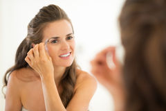 Young woman shaping eyebrows in bathroom Stock Photos