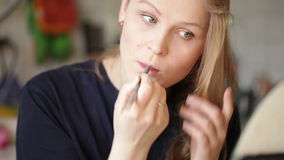 Young woman shaping her eyebrows. Close up portrait with natural morning sunlight. stock video