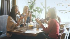Young woman sharing something on her mobile phone with three attractive laughing girl friends