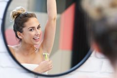 Young woman shaving armpits in bathroom stock image