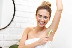 Young woman shaving armpits in bathroom stock images