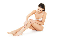 Young woman shaving her legs Royalty Free Stock Photo
