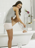 A young woman shaving her legs. A smiling young woman shaving her legs over the bath stock image