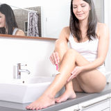 Young woman shaving her legs at washbasin Stock Photo