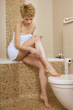 Young woman shaving her legs Stock Photos