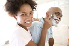 Young woman shaving young man in bathroom, smiling, portrait Stock Photography